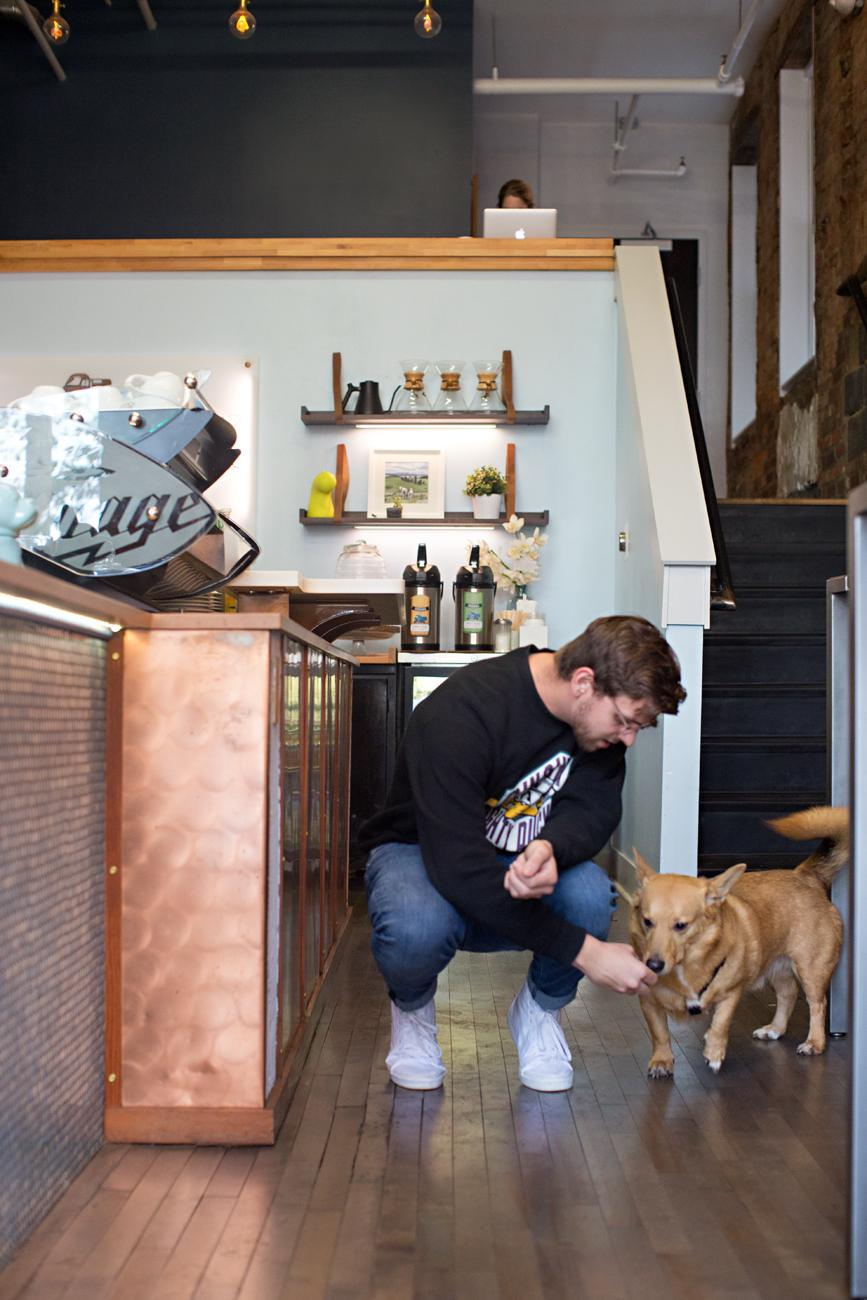 Trevor Biggs, barista, and Buckley, a corgi, enjoying Urbana Café / Image: Sarah Parisi Dowlin // Published: 11.7.18