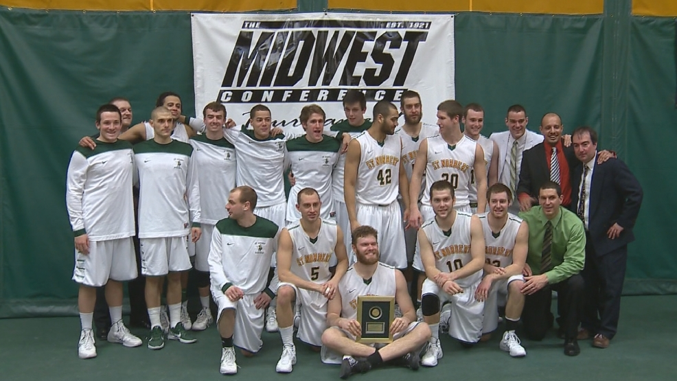 The St. Norbert men's basketball team poses with their championship trophy Saturday.