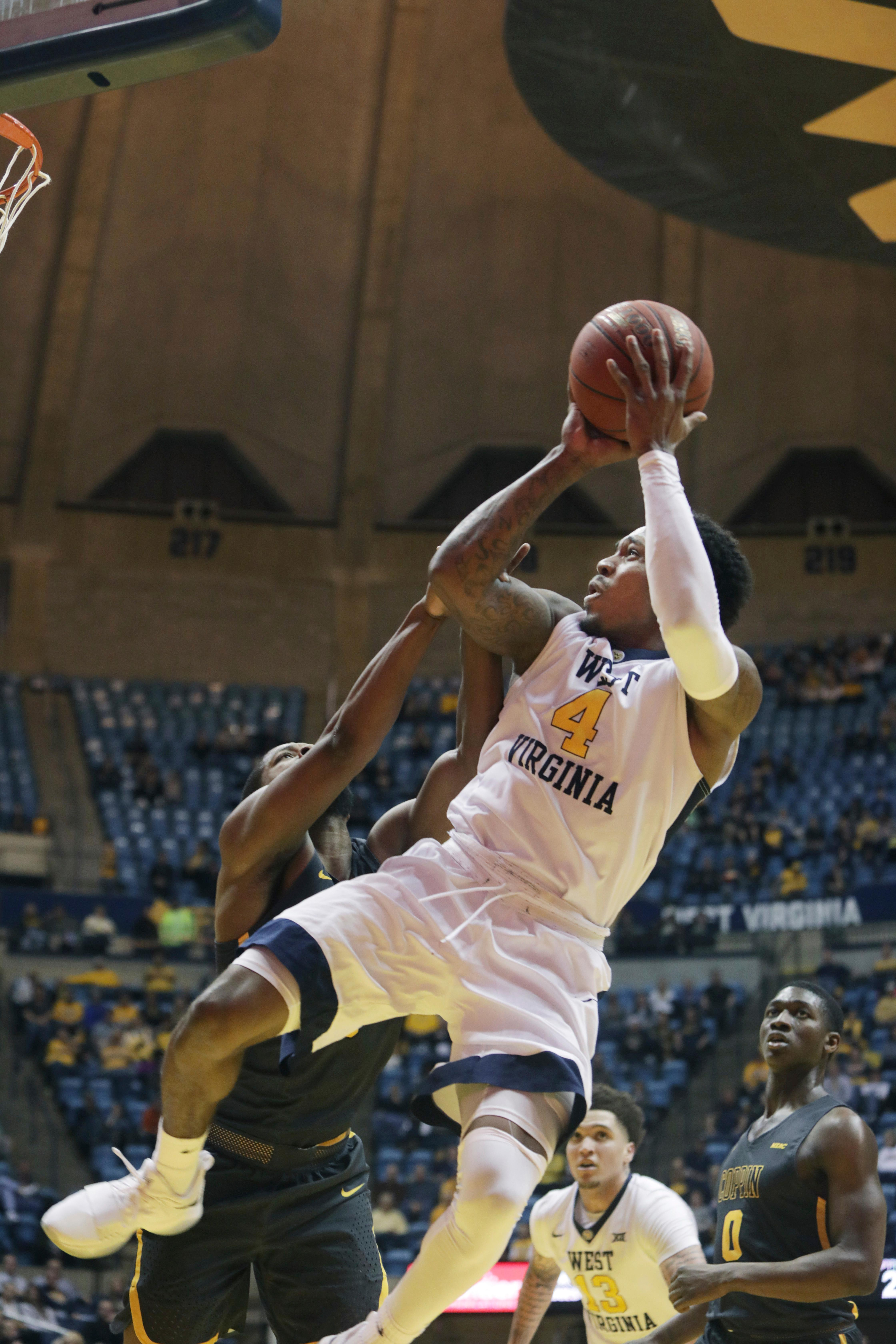 West Virginia guard Daxter Miles Jr. (4) is fouled by Coppin State guard Tre' Thomas (4) during the second half of an NCAA college basketball game Wednesday, Dec. 20, 2017, in Morgantown, W.Va. (AP Photo/Raymond Thompson)