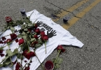"A shirt reading ""hands up don't shoot"" is covered with roses Tuesday, Aug. 19, 2014, at the spot Michael Brown was killed by police Aug. 9 in Ferguson, Mo. (AP Photo/Charlie Riedel)"