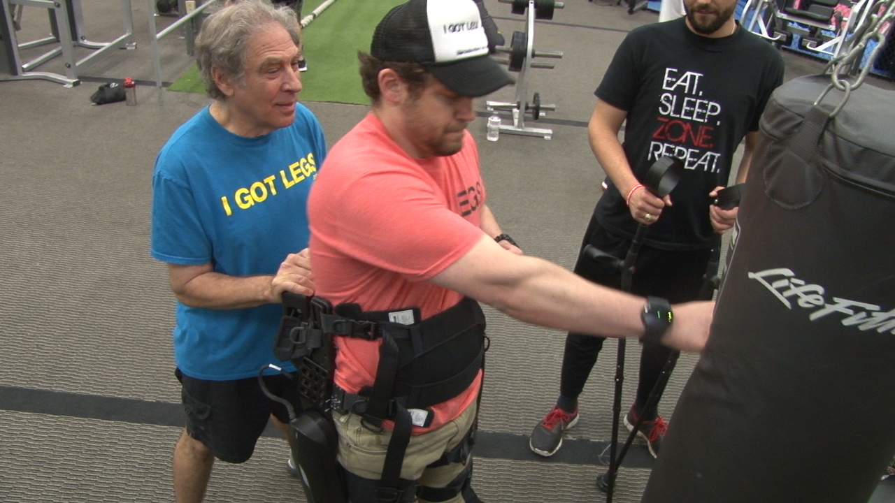 Adam Gorlitsky, assisted by his father Stan, works out as he gets used to his exoskeleton before the Cooper River 10k. (Photos courtesy Jeremy Sullivan)