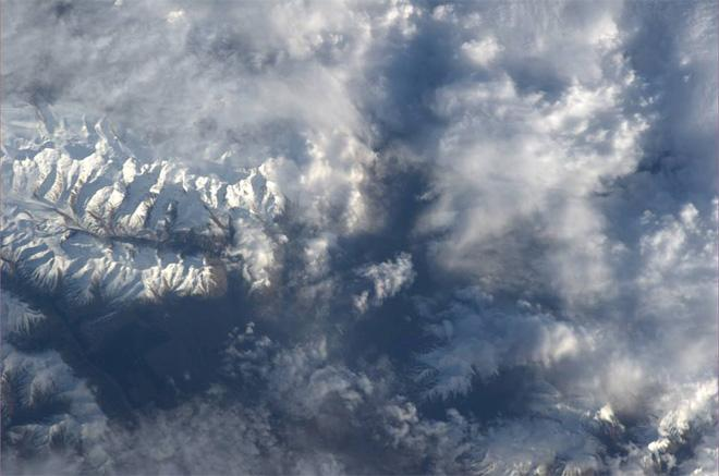 Snow covers the mountains of New Zealand, peeking among the clouds (Photo & Caption: Luca Parmitano, NASA)