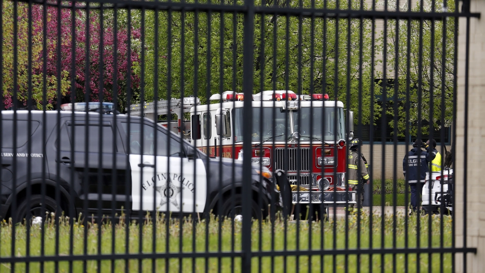 Police and firefighters are seen at the Chicago Terminal Radar Approach Control, or TRACON, center in Elgin, Ill., Tuesday, May 13, 2014, after smoke at the radar facility forced a ground stop to all incoming and outgoing flights at both of Chicago's airports. The Federal Aviation Administration says all its personnel at the facility were evacuated. (AP Photo/Daily Herald, Brian Hill)