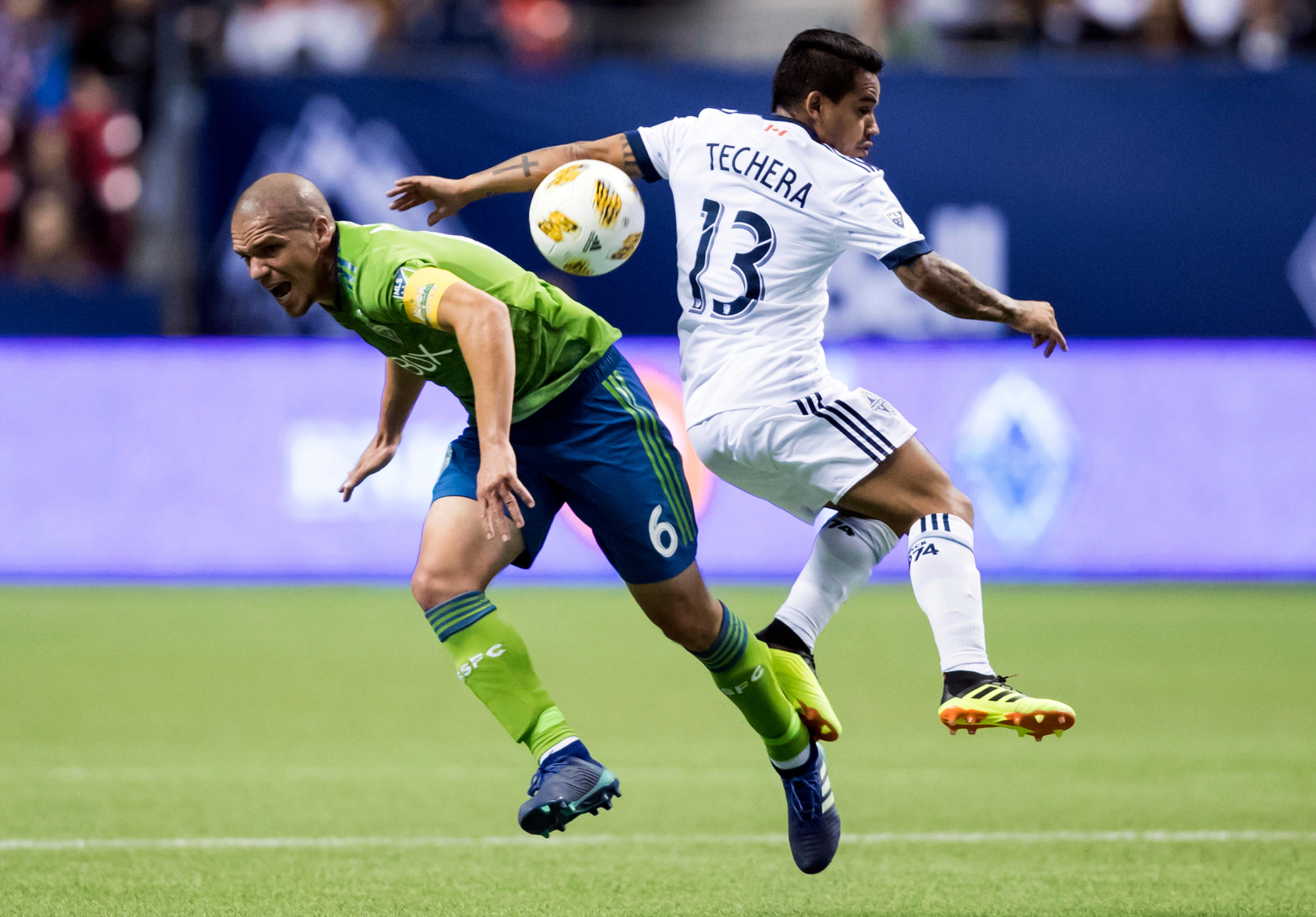 Seattle Sounders' Osvaldo Alonso (6) and Vancouver Whitecaps' Cristian Techera (13) collide during the first half of an MLS soccer match, Saturday, Sept. 15, 2018, in Vancouver, British Columbia. (Darryl Dyck/The Canadian Press via AP)