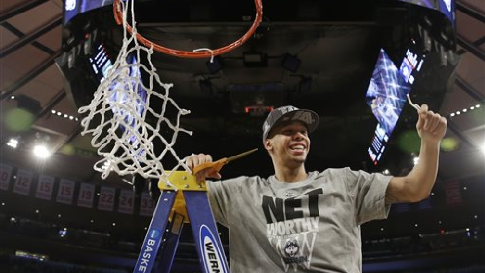 Connecticut's Shabazz Napier smiles after cutting the net after a regional final against Michigan State in the NCAA college basketball tournament Sunday, March 30, 2014, in New York. Connecticut won the game 60-54. (AP Photo/Seth Wenig)