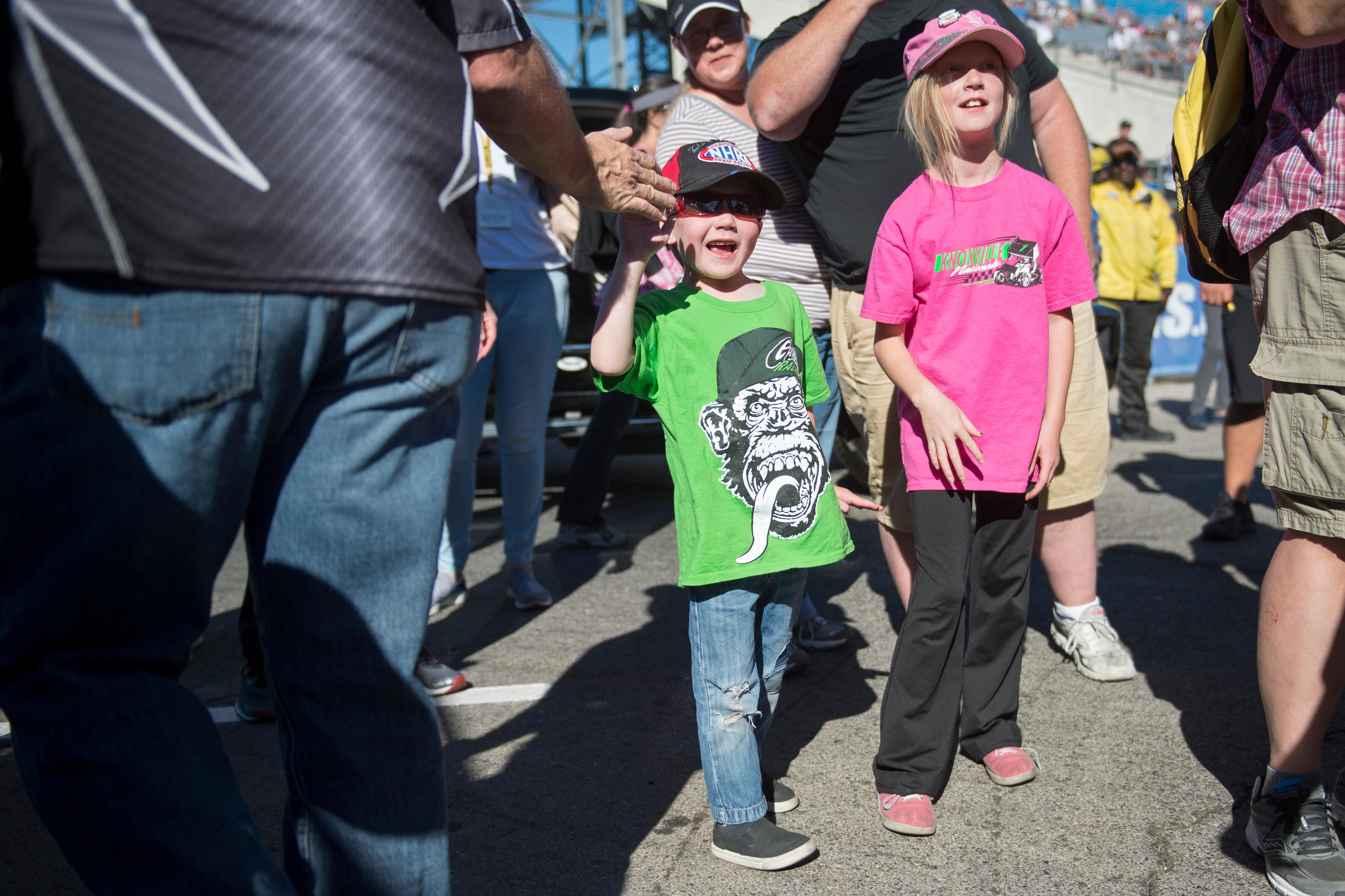 Siblings Tyler, left, and Danielle Seaman from Salt Lake City get high-fives from drivers before the start of the NHRA Toyota Nationals Sunday, October 29, 2017, at The Strip at the Las Vegas Motor Speedway. CREDIT: Sam Morris/Las Vegas News Bureau