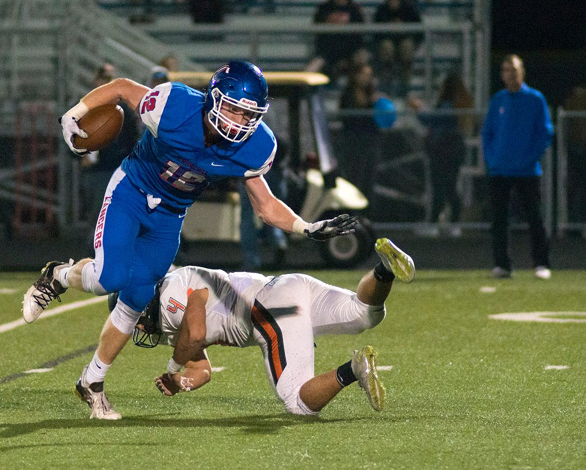Churchill Lancers Jax Arnold (#12) carries the ball past Crater Comets defense. Churchill defeated Crater 63-21 on Friday at their homecoming game. Churchill remains undefeated with a conference record of 9-0. Photo by Rhianna Gelhart, Oregon News Lab