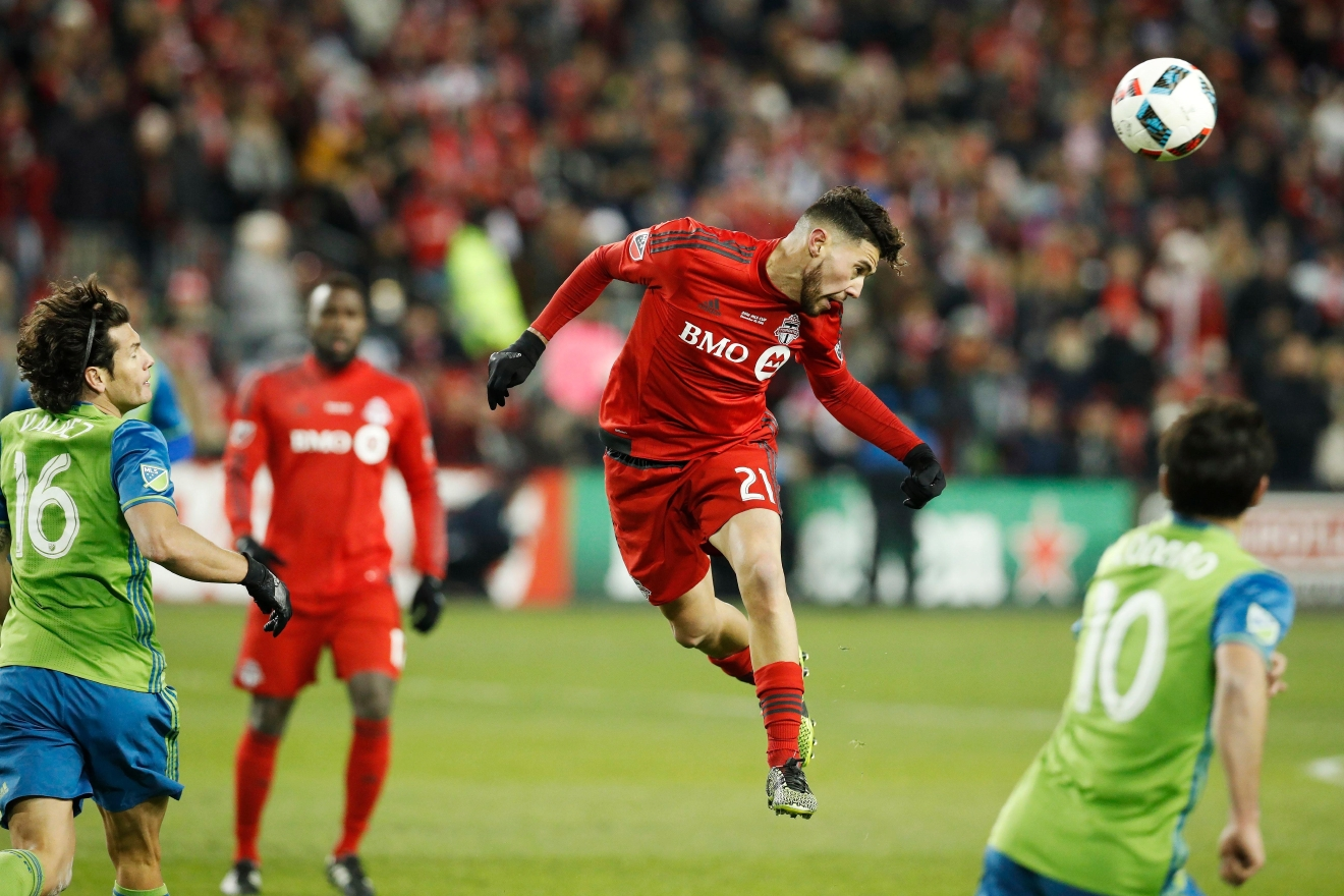 Toronto FC midfielder Jonathan Osorio (21) heads the ball ahead of Seattle Sounders midfielder Nicolas Lodeiro (10) during first-half MLS Cup final soccer action in Toronto, Saturday, Dec. 10, 2016. (Mark Blinch/The Canadian Press via AP)