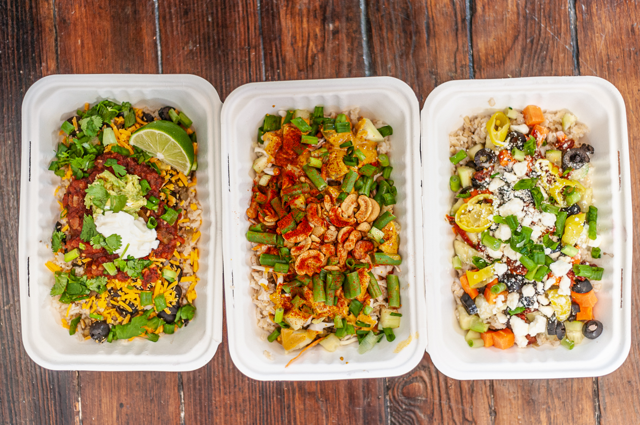 Spicy Thai Bowl (brown rice and lentils topped with cabbage, carrots, cucumbers, green beans, curry cashews, scallions, paprika, homemade spicy Thai sauce, and lime), Fiesta Bowl (brown rice and lentils topped with cheddar cheese, black olives, organic salsa, mashed avocado, cilantro, scallions, and lime) and Mediterranean Bowl (brown rice and lentils topped with cucumbers, black olives, carrots, pepperoncinis, sundried tomatoes, scallions, feta, and house tzatziki sauce) / Image: Kellie Coleman // Published: 12.27.20