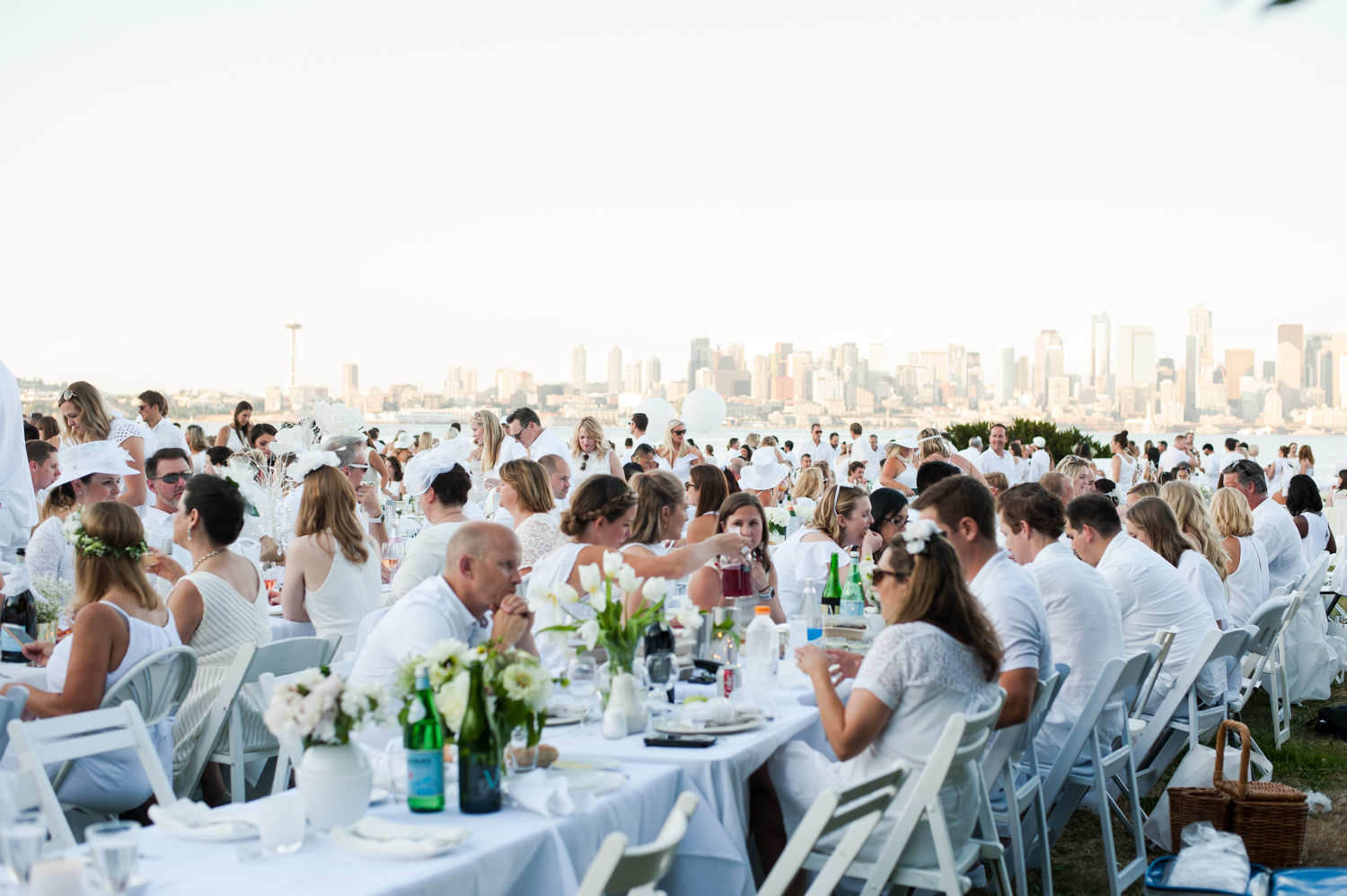 Diner en Blanc launched 30 years ago in Paris as a secret dining experience. Now events take place throughout the world,{ }where guests gather at a secret location to share a gourmet meal at the heart of one of their city's most beautiful locations. You don't know where you'll be going until day-of, and you have to bring your own table, chairs, a picnic basket, tablecloth, napkins, gourmet meal, dish-ware and glassware. The Seattle dinner's last minute location was revealed at around 6:45 p.m., and by 7:30 everyone was seated and ready at Don Armeni Park on Alki Beach. (Image: Elizabeth Crook/ Seattle Refined){ }