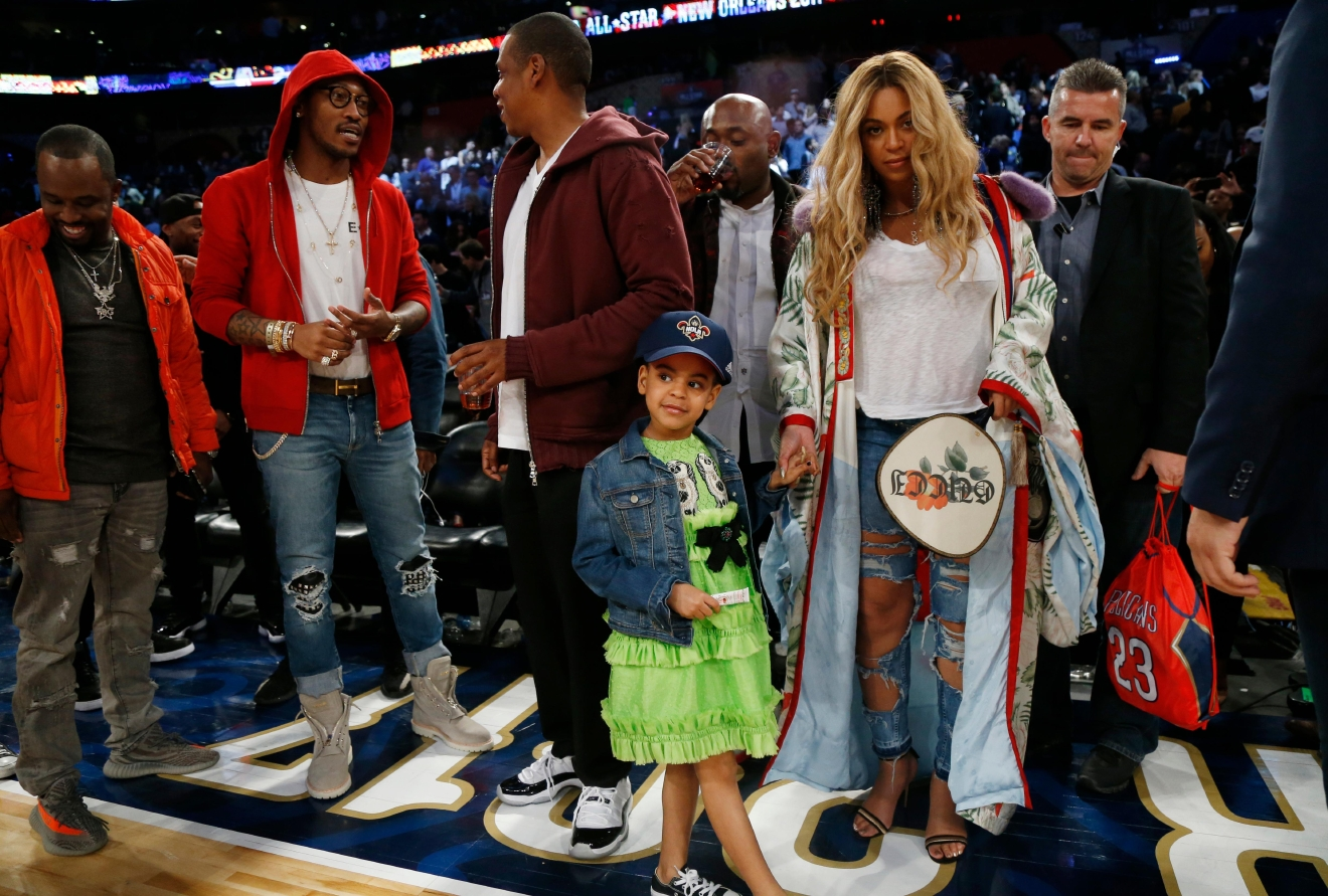 Beyonce holds the hand of her daughter Blue Ivy Carter, while her husband, rapper Jay Z, talks in the background, after the NBA All-Star basketball game in New Orleans, Sunday, Feb. 19, 2017. (AP Photo/Max Becherer)