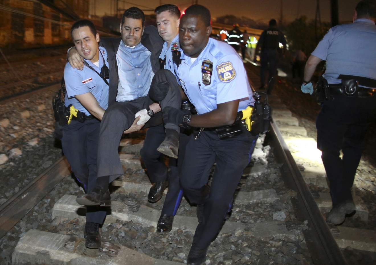 FILE - In this Tuesday, May 12, 2015 file photo, emergency personnel help a passenger in Philadelphia after the derailment in Philadelphia of an Amtrak train headed to New York. The National Transportation Safety Board is scheduled to meet Tuesday, May 17, 2016, to detail the probable cause of last year's fatal derailment. (AP Photo/Joseph Kaczmarek, File)