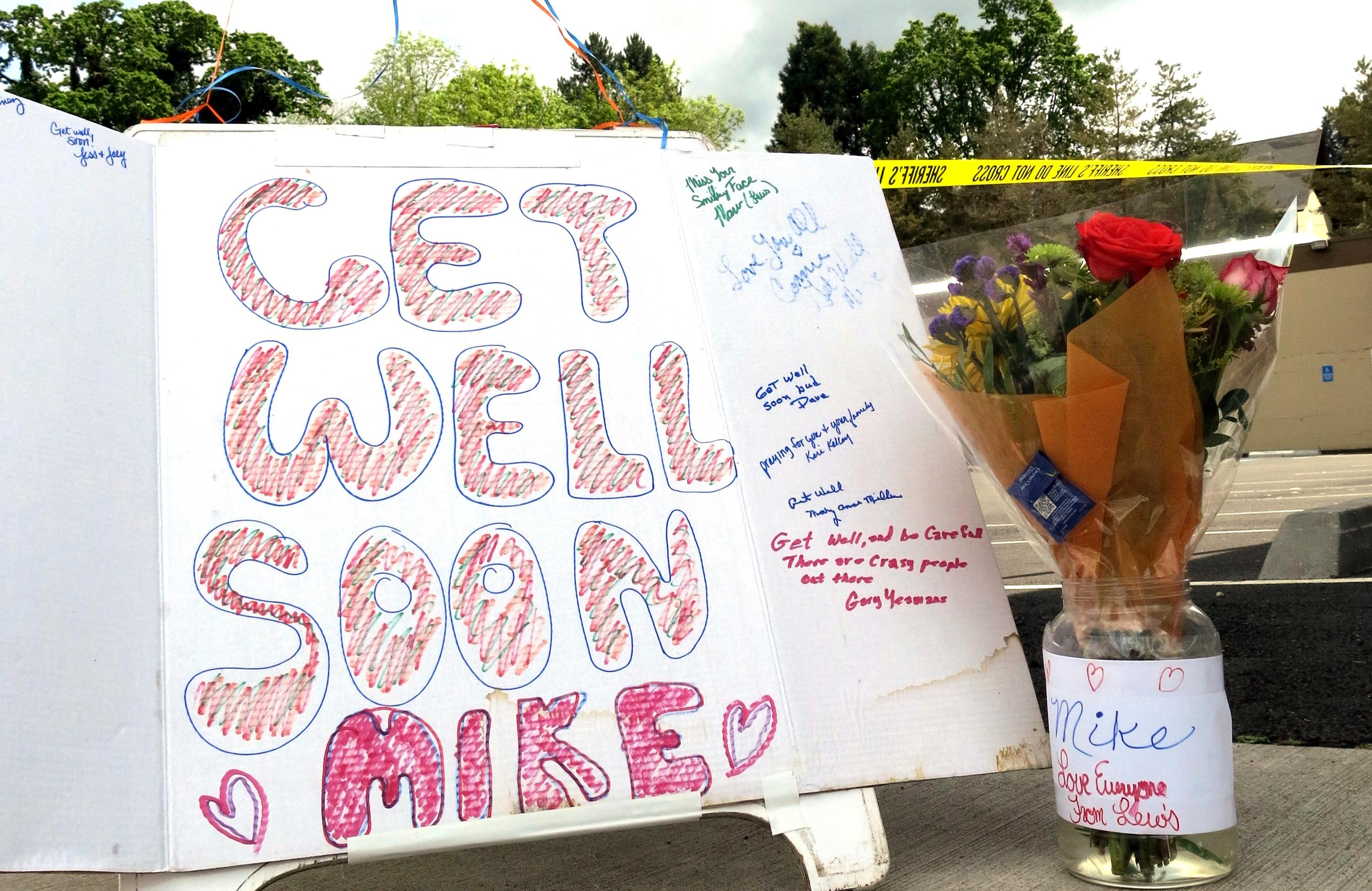 Well-wishing messages and flowers for an injured employee are shown outside a grocery store in Estacada, Ore., Monday, May 15, 2017. Police say a man carrying what appeared to be a human head stabbed an employee at the grocery store. (AP Photo/Gillian Flaccus)