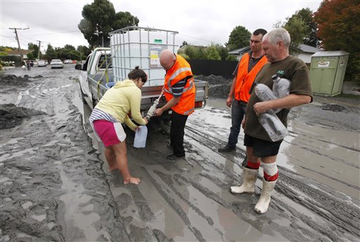 A resident fills her water container while another waits in their earthquake damaged suburb in Christchurch, New Zealand. / AP photo