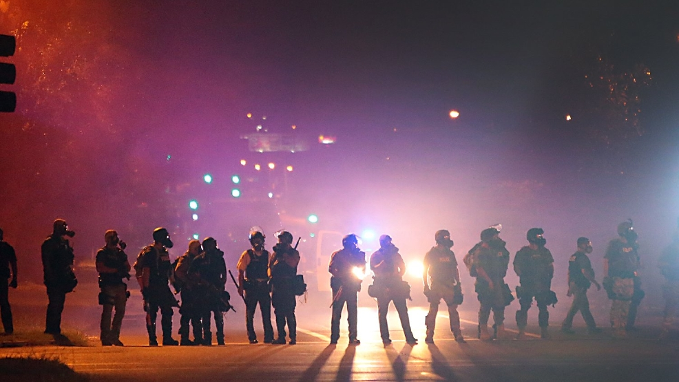 Police officers work their way north on West Florissant Avenue in Ferguson, Mo., clearing the road of people Wednesday, Aug. 13, 2014. (AP Photo/St. Louis Post-Dispatch, Robert Cohen)