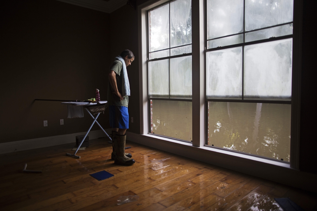 David Key looks at water out of his master bedroom windows in his flooded home in Prairieville, La., Tuesday, Aug. 16, 2016. Key, an insurance adjuster, fled his home as the flood water was rising with his wife and three children and returned today to assess the damage. (AP Photo/Max Becherer)