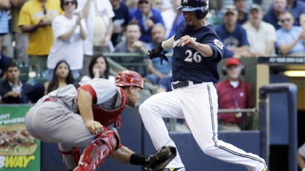 Milwaukee Brewers' Kyle Lohse slides safely past Cincinnati Reds catcher Devin Mesoraco during the fifth inning of a baseball game Wednesday, July 23, 2014, in Milwaukee. Lohse scored from first on a ball hit by Carlos Gomez. (AP Photo/Morry Gash)