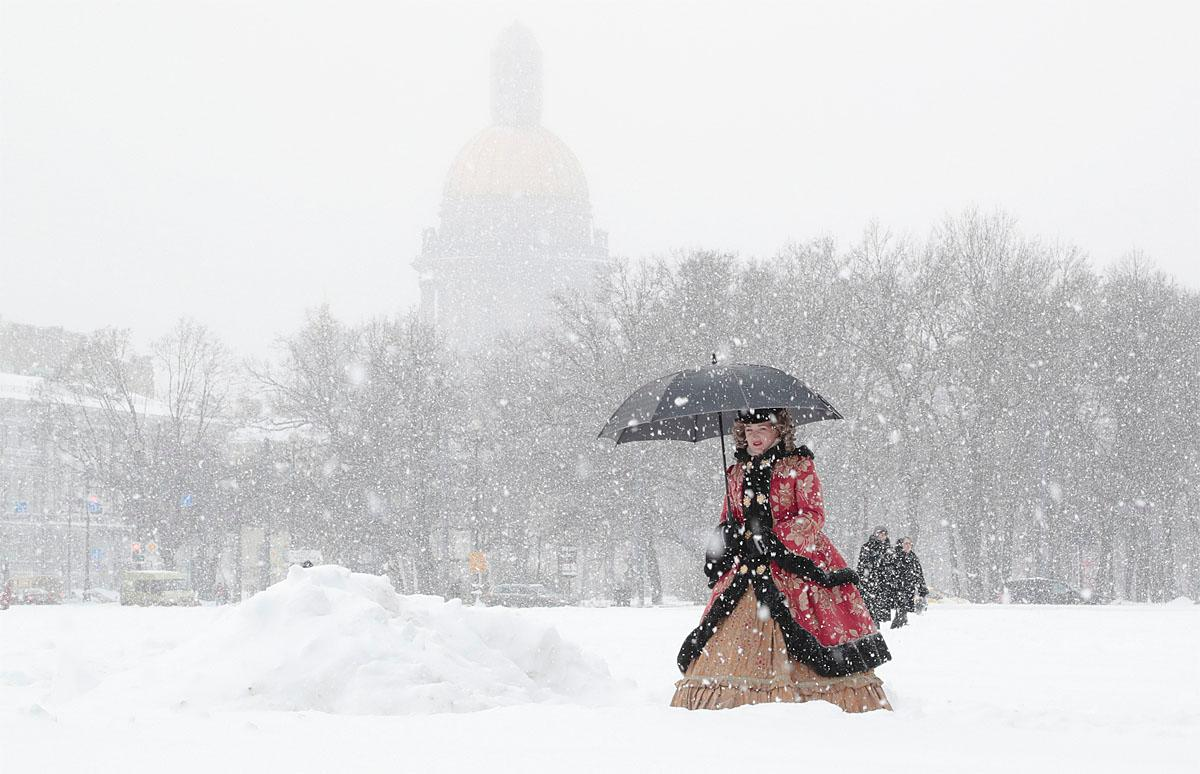 An actress dressed in a period costume walks through the snow in St. Petersburg, Russia, Tuesday, Nov. 8, 2016. Low temperatures caused two days of snowfall in St. Petersburg. (AP Photo/Dmitri Lovetsky)