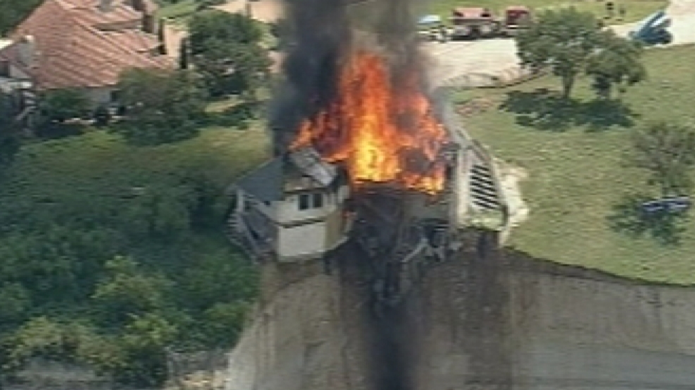 Firefighters burn a luxury house that's teetering atop a crumbling 75-foot cliff over Lake Whitney, Friday, June 13, 2014.