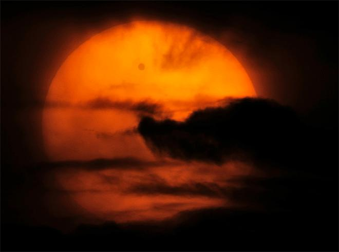 Venus is seen passing in front of the sun in the clouds, in this image taken through a telescope, from Losevo village, north of St. Petersburg, Russia, Wednesday, June 6, 2012. People around the world turned their attention to the daytime sky on Tuesday and early Wednesday in Asia to make sure they caught the rare sight of the transit of Venus. (AP Photo/Dmitry Lovetsky)