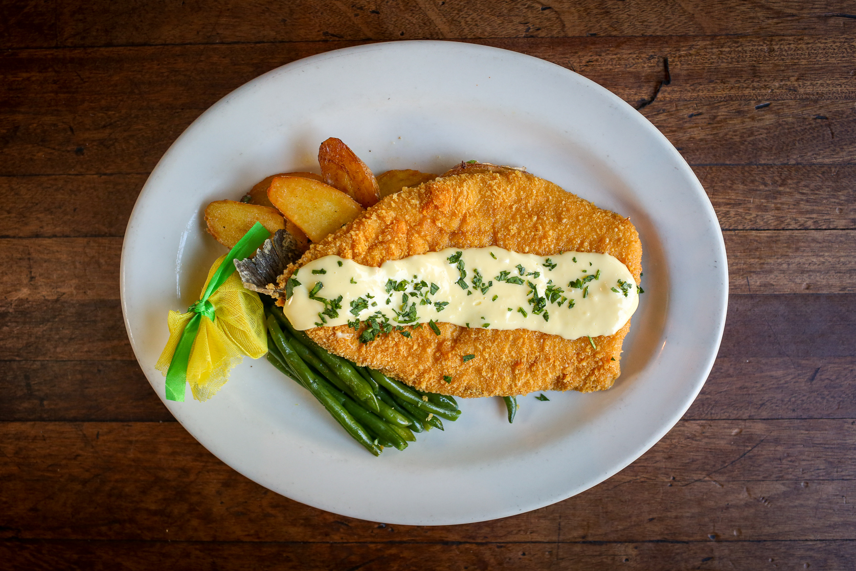 Trout Parmesan served with crispy new potatoes, sautéed green beans and hollandaise sauce (Amanda Andrade-Rhoades/DC Refined)