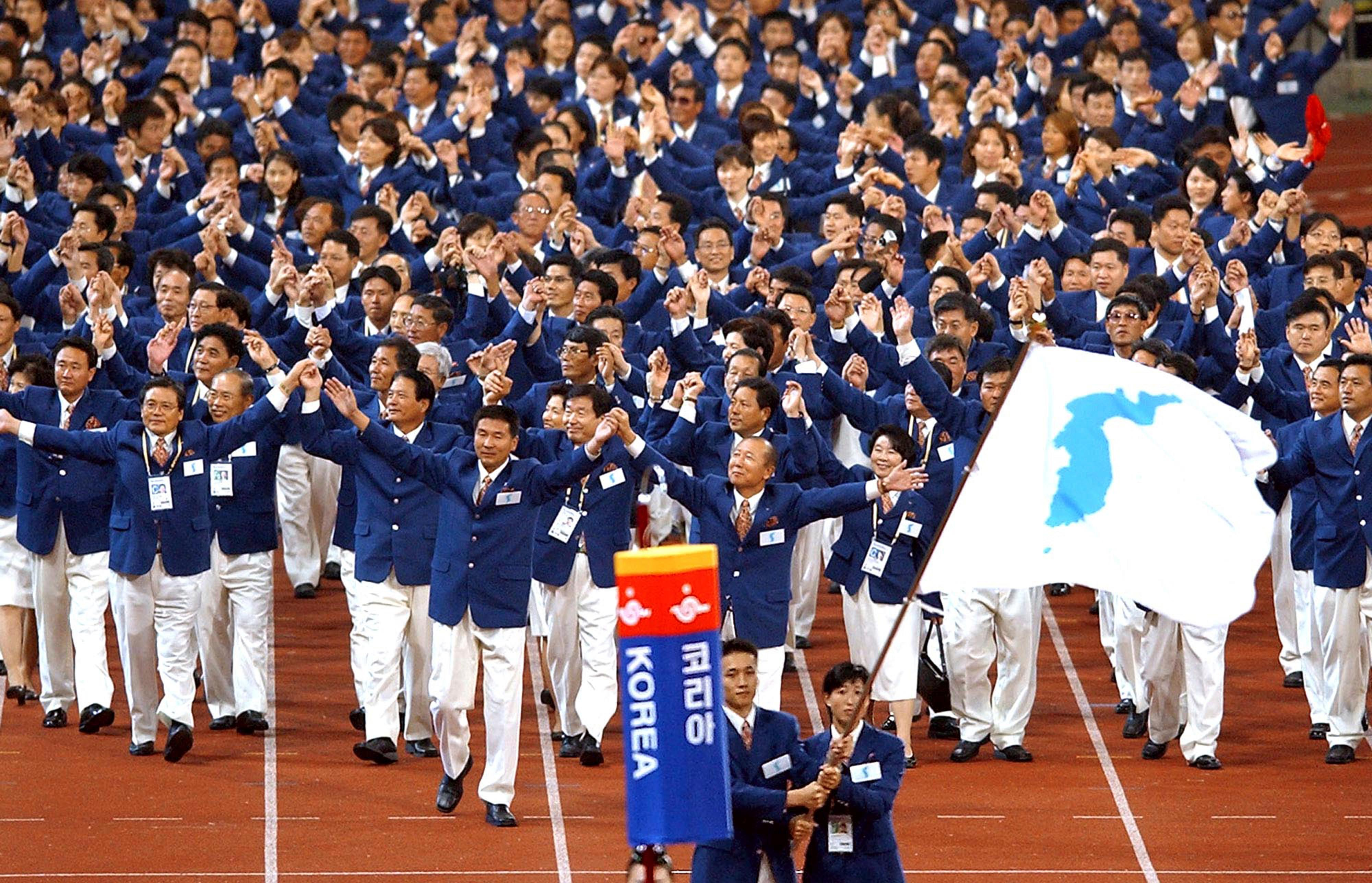 "FILE - In this Sept. 29, 2002 file photo, athletes from North and South Korea march together, led by a unification flag, during an opening ceremony for the 14th Asian Games in Busan, South Korea. During South and North Korea's talks at the border in about a week Wednesday, Jan. 17, 2018, senior officials from the two Koreas reached a package of deals including fielding a joint women's hockey team and conducting a joint march under a ""unification flag"" depicting their peninsula during the opening ceremony, according to Seoul's Unification Ministry.(Yonhap via AP, File)"