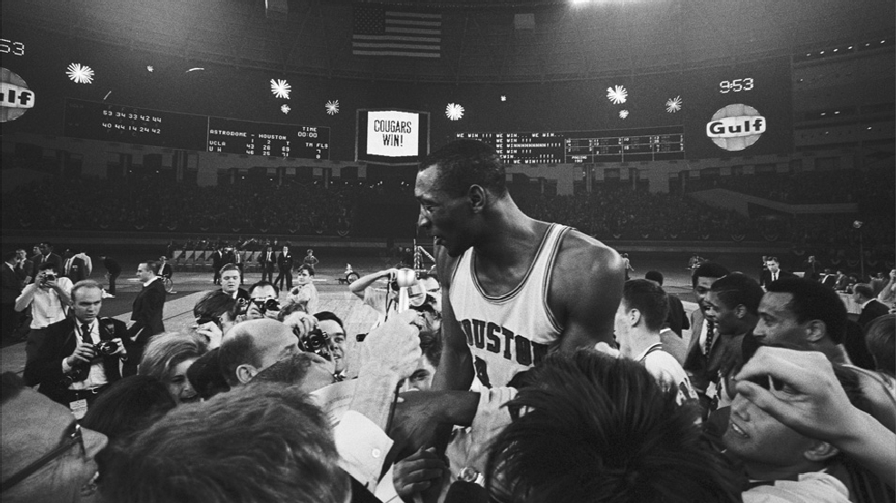 Houston's Elvin Hayes is carried from the court by jubilant fans after Houston scored a 71-79 upset over the UCLA Bruins. Amidst a fireworks display in lights, the Astrodome scoreboard reads 'Cougars win.' The game pitted the top two teams in the nation. (Photo by Bettmann via Getty Images)
