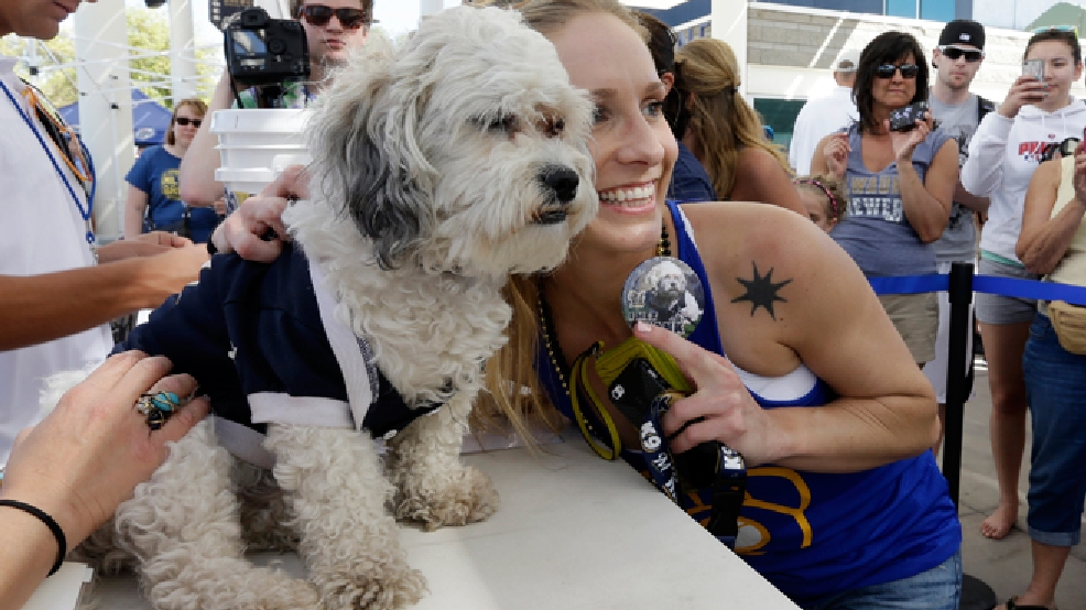 Ashley Alfredson, of Kenosha, poses for a photo with the Milwaukee Brewers unofficial mascot, Hank, during an exhibition game against the Cincinnati Reds, Saturday, March 15, 2014, in Phoenix. (AP Photo/Morry Gash)