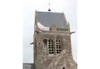In this photo dated Friday, April 25, 2014, a dummy paratrooper representing a WWII paratrooper from the 82nd Airborne hangs on the belltower of Sainte Mere Eglise, in Normandy, France. During the drop, American paratrooper John Steele's parachute got caught on the church spire. For two hours, Steele hung there, feigning death before being taken prisoner by the Germans. Today, a dummy paratrooper hangs from the spire in his honor. (AP Photo/David Vincent, file)