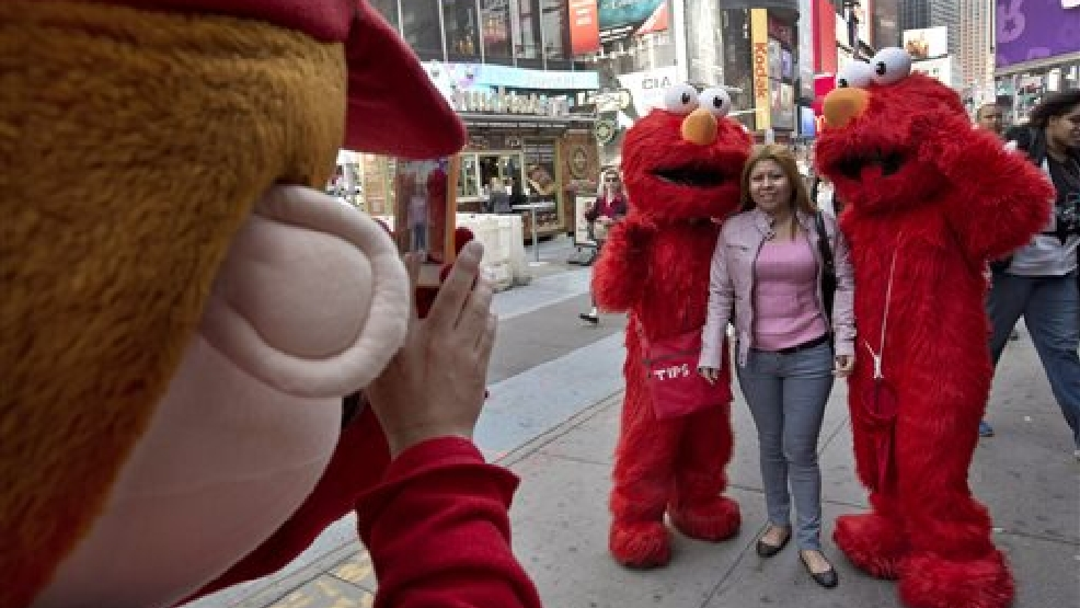 In this April 9, 2013 file photo, a Super Mario character, left, uses a woman's mobile phone camera to photograph her with a pair of Elmo characters in New York's Times Square. A New York City Council member is drafting legislation to regulate the costumed characters who roam Times Square. The bill being proposed by Councilman Dan Garodnick would require that the costumed performers be licensed and go through a background check. There have been a number of troublesome incidents involving costumed figures who try to make a living by charming tourists. (AP Photo/Richard Drew, File)