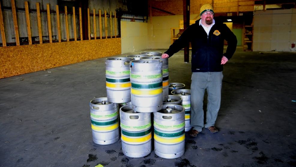 Stillmank Brewing Co. owner Brad Stillmank stands by empty kegs in his company's new building.