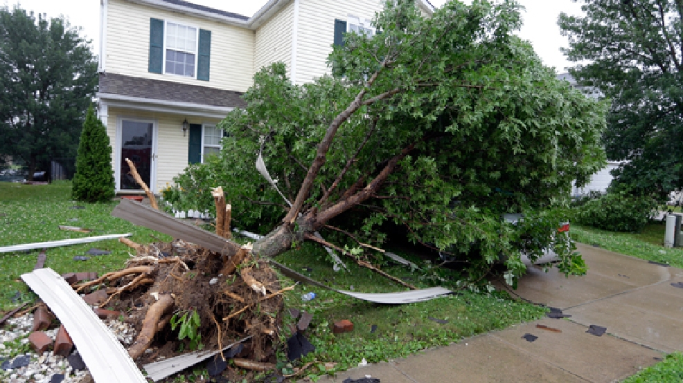 A tree uprooted by a storm covers a car in front of home in Indianapolis, Ind., Tuesday, June 24, 2014. National Weather Service meteorologist Mike Ran says the tornado struck Tuesday afternoon just southwest of Indianapolis but was no longer on the ground. (AP Photo/Michael Conroy)