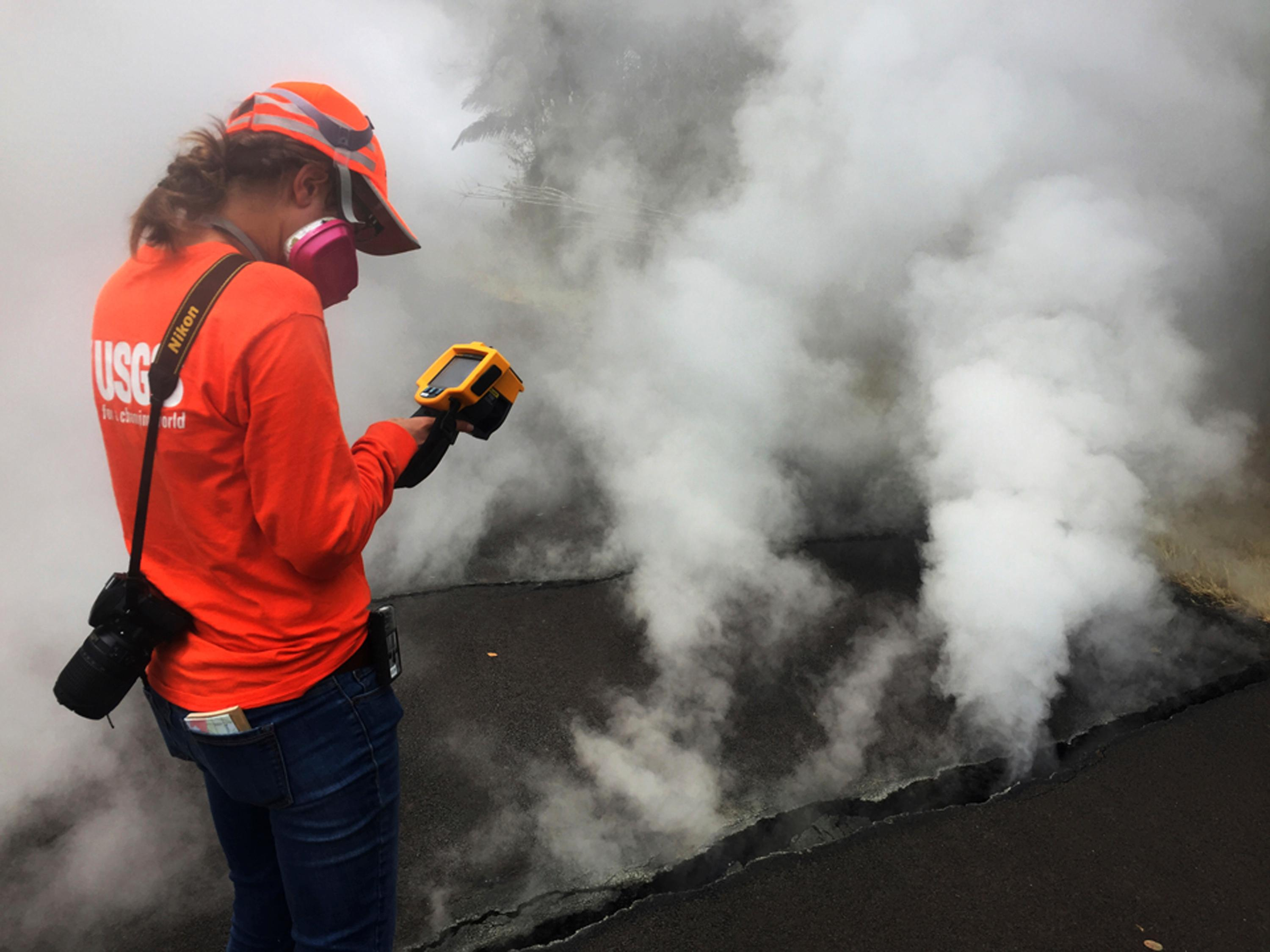 This photo provided by the U.S. Geological Survey shows a Hawaii Volcano Observatory geologist recording a temperature of 103 degrees C (218 degrees F) at a crack along Nohea Street in Leilani Estates near the town of Pahoa, Hawaii, Wednesday, May 9, 2018.{ } (U.S. Geological Survey via AP)