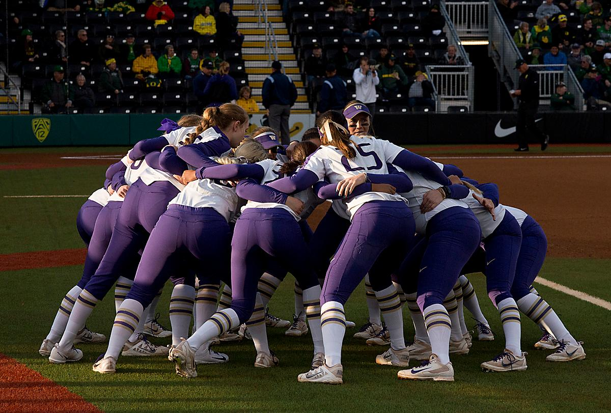 The University of Washington Huskies get pumped up before Game Two against the Oregon Ducks. In Game Two of a three-game series, the University of Oregon Ducks softball team defeated the University of Washington Huskies 4-1 Friday night in Jane Sanders Stadium. Danica Mercado (#2), Alexis Mack (#10) and Mia Camuso (#7) all scored in the win, Mack twice. The Ducks play the Huskies for the tie breaker on Saturday with the first pitch at noon. Photo by Dan Morrison, Oregon News Lab