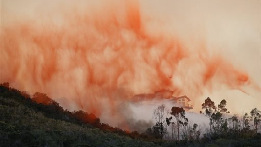 A plane drops fire retardant over a hot spot on Wednesday, May 14, 2014, in San Marcos, Calif. Flames engulfed suburban homes and shot up along canyon ridges in one of the worst of several blazes that broke out Wednesday in Southern California. (AP Photo)