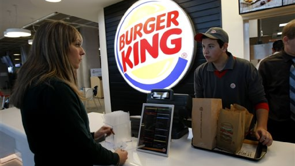 In a Saturday, Dec. 22, 2012 file photo, a customer purchases a meal at a Burger King restaurant in Marseille-Provence airport, in Marignane, France. Burger King is in talks to buy Tim Hortons in hopes of creating a new, publicly traded company with its headquarters in Canada. (AP Photo/Claude Paris, File)
