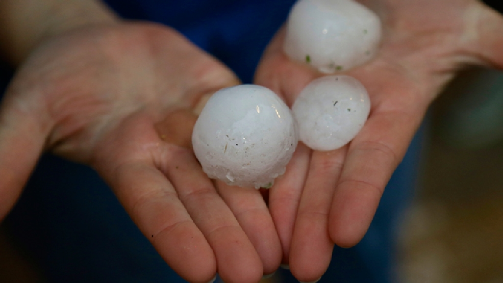 Mindy Rump holds golf ball-sized hail stone for a photographer following a severe thunderstorm in Blair, Neb., Tuesday, June 3, 2014. (AP Photo/Nati Harnik)