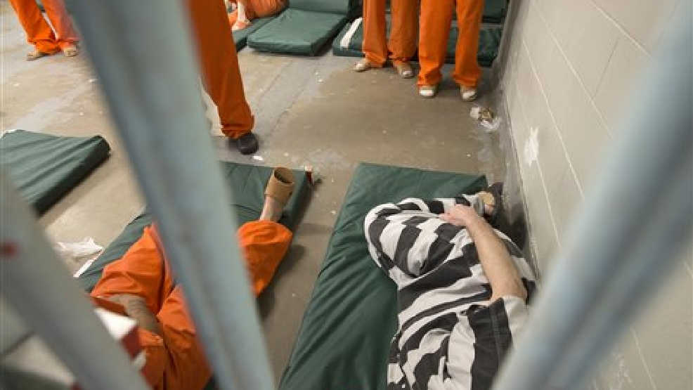 Inmates wearing a mix of orange and striped jumpsuits are lodged in a cell at the Saginaw County Jail, Friday, July 18, 2014 in Saginaw, Mich. The Saginaw County Sheriff's Department has purchased new jumpsuits, with black and white stripes, for some of the inmates at the jail. (AP Photo/The Saginaw News/MLive.com, Jeff Schrier)