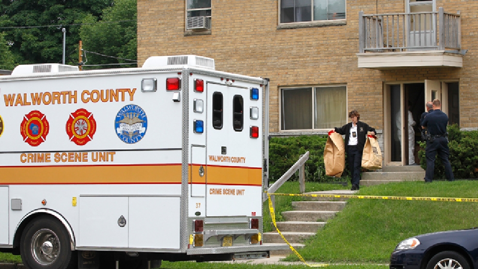 In this photo taken on Wednesday, June 25, 2014, Walworth County investigators carry bags full of material from an apartment in West Allis, Wis., after picking up a suspect allegedly involved in two murders where the bodies were found in suitcases along a rural road in Geneva several weeks ago. (AP Photo/Milwaukee Journal-Sentinel, Gary Porter)