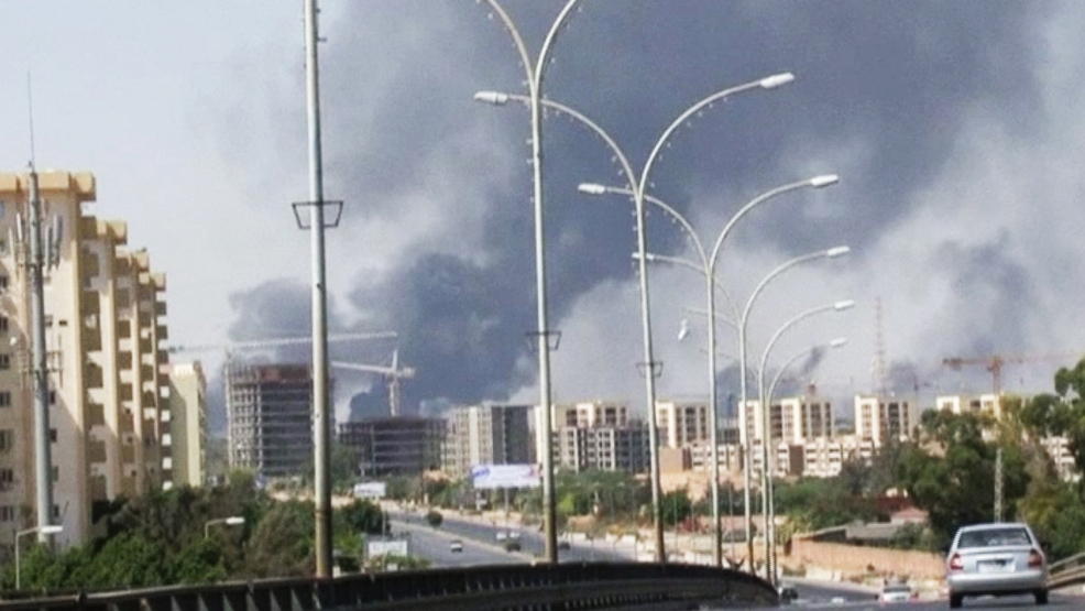 In this Sunday, July 13, 2014 file image made from video by The Associated Press, smoke rises from the direction of Tripoli airport in Tripoli, Libya. The United States shut down its embassy in Libya on Saturday, July 26, 2014, and evacuated its diplomats to neighboring Tunisia under U.S. military escort amid a significant deterioration in security in Tripoli as fighting intensified between rival militias, the State Department said. (AP Photo/File)