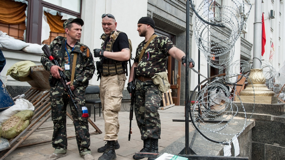Pro-Russian armed men stand at the city hall in the eastern Ukraine city of Luhansk on Monday, May 12, 2014. (AP Photo/Evgeniy Maloletka)