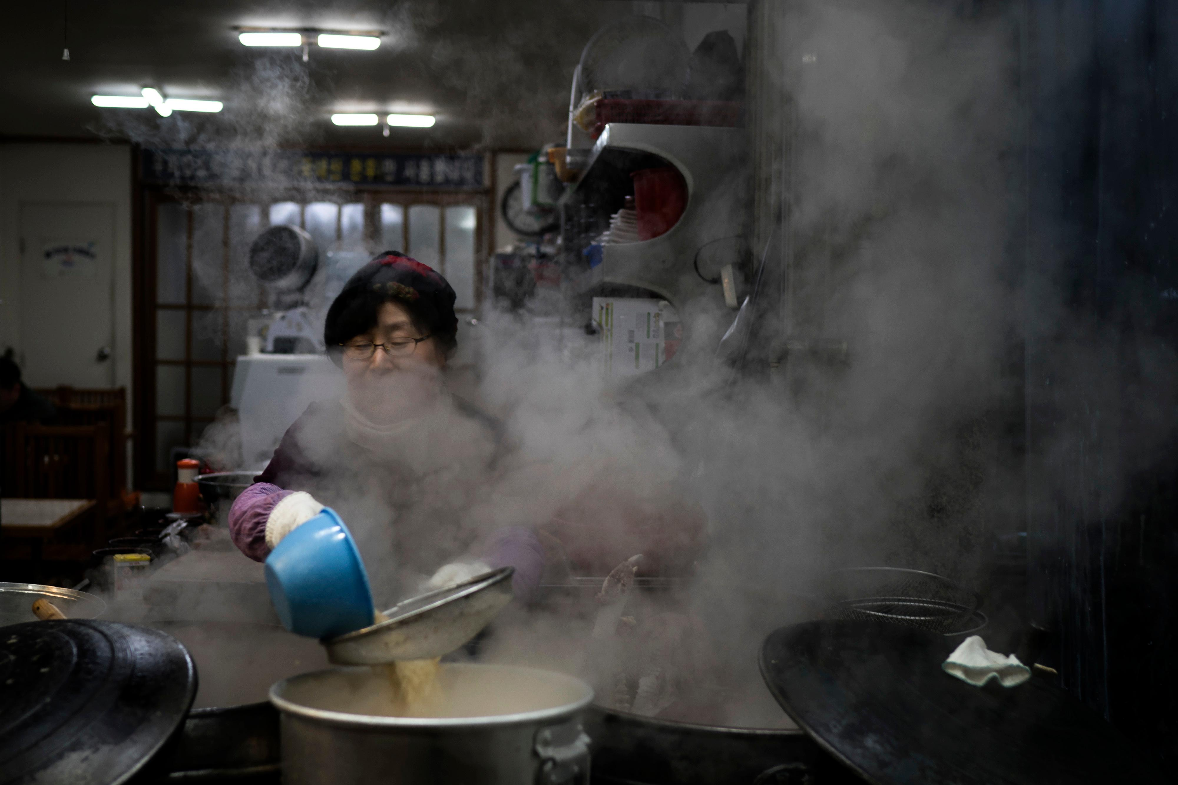 A woman cooks at a restaurant in Gangneung, South Korea, Monday, Feb. 12, 2018.  Korean food is some of the world's finest - savory, salty soups with fish so tender it falls off the bone; thick slabs of grilled pork and beef backed with spicy kimchi that many Korean grandmothers swear cures the common cold. But it's very different from what many foreign Olympians are used to. (AP Photo/Felipe Dana)