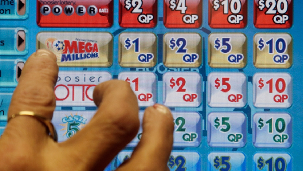 FILE - In this Dec. 17, 2013 file photo a clerk prepares to operate a lottery machine to print out Mega Millions lottery tickets for a customer in Muncie, Ind. (AP Photo/Darron Cummings, File)