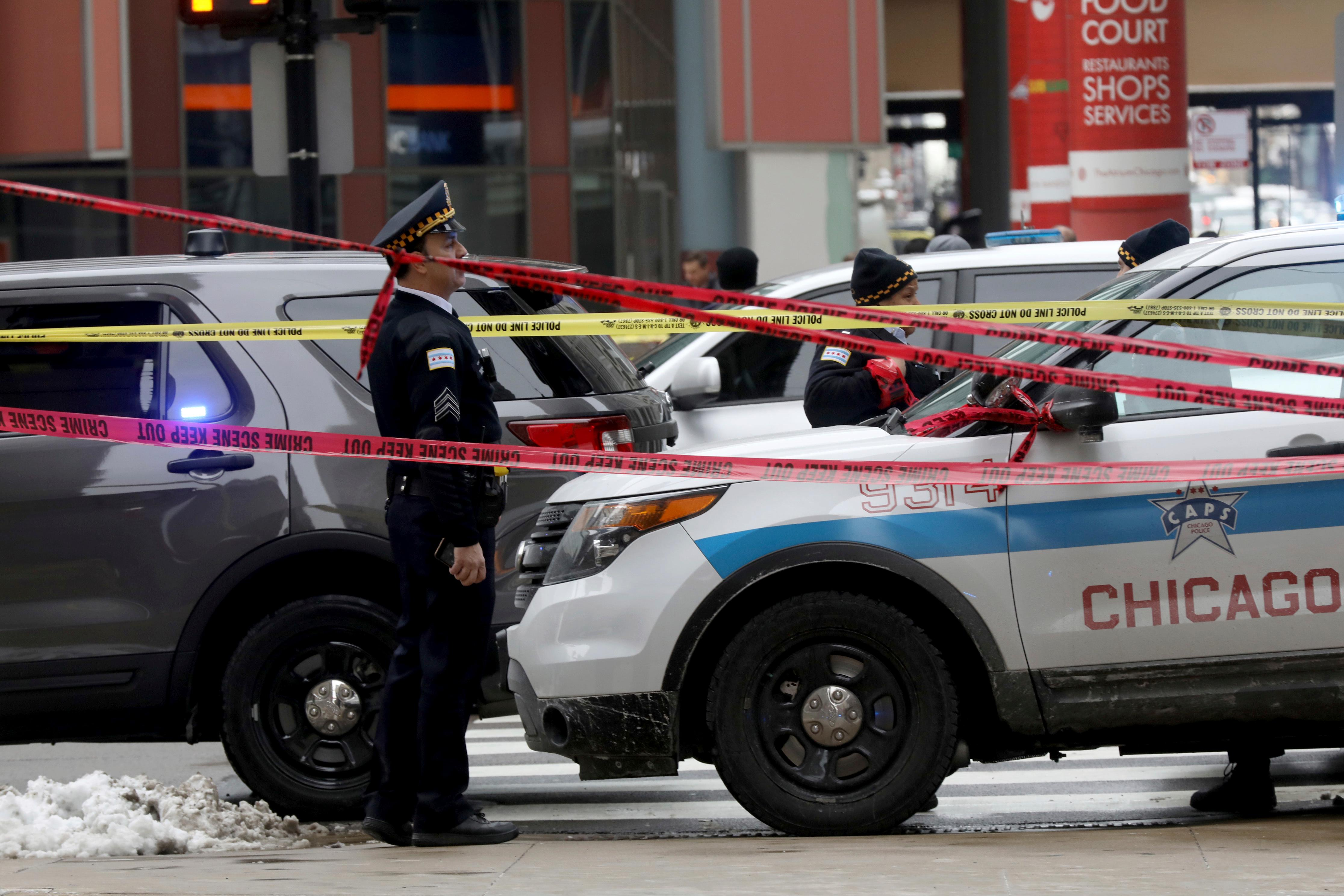 Police guard the scene where an off-duty officer was shot while assisting a tactical team at a state government office building, Tuesday, Feb. 13, 2018, in Chicago. (John J. Kim/Chicago Tribune via AP)