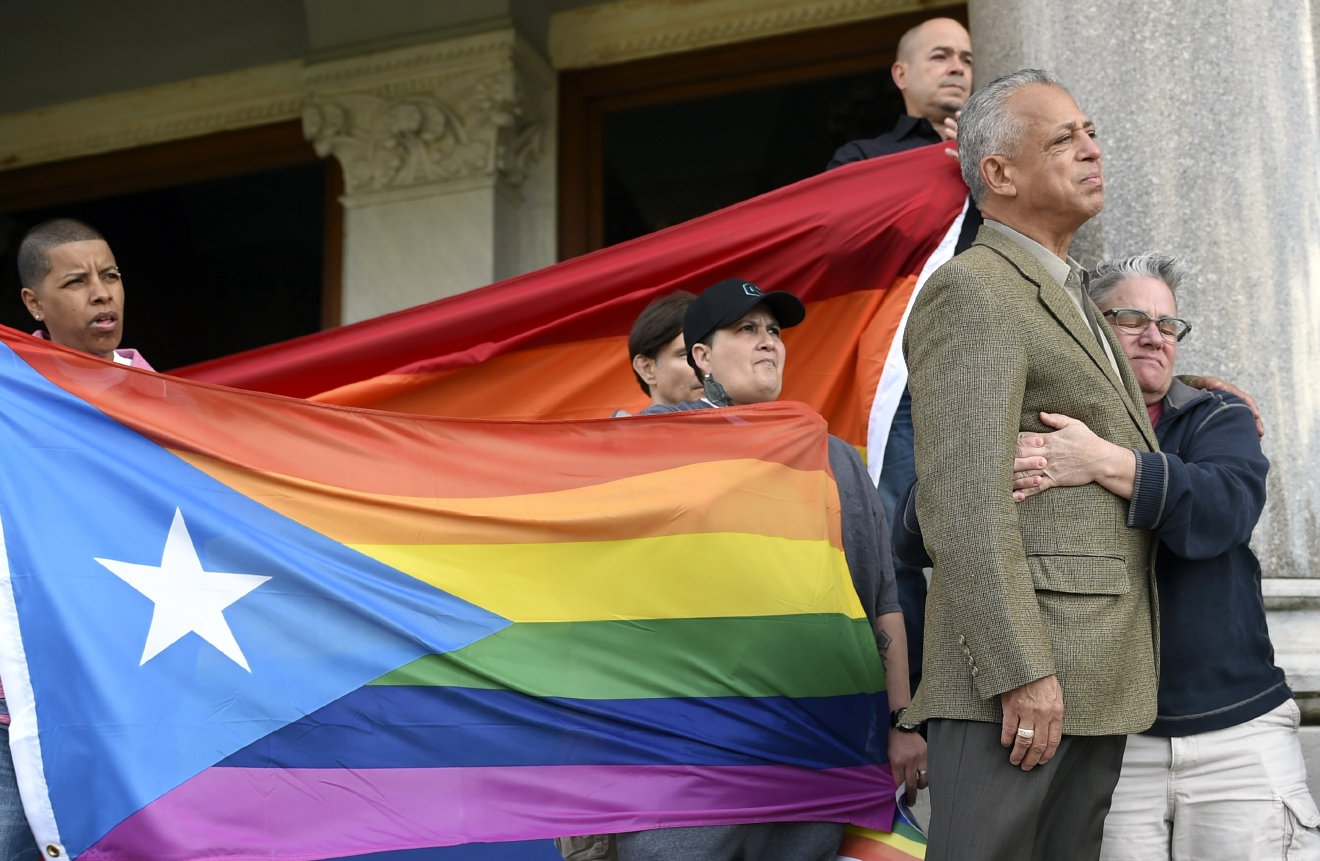 Former Hartford Mayor Pedro Segarra and Shawn Lang of Hartford embrace after Segarra spoke Sunday, June 12, 2016, during a vigil organized by the state's Muslim and lesbian, gay, bisexual and transgender communities Sunday evening on the steps of the state Capitol building in reaction to the mass shooting in Orlando, Fla,  Holding gay pride flags behind Segarra and Lang are from left, Fioroella Hidalgo, Becky Muniz (hat), Stephen Vetter and Charlie Ortiz.   (John Woike/Hartford Courant via AP) MANDATORY CREDIT