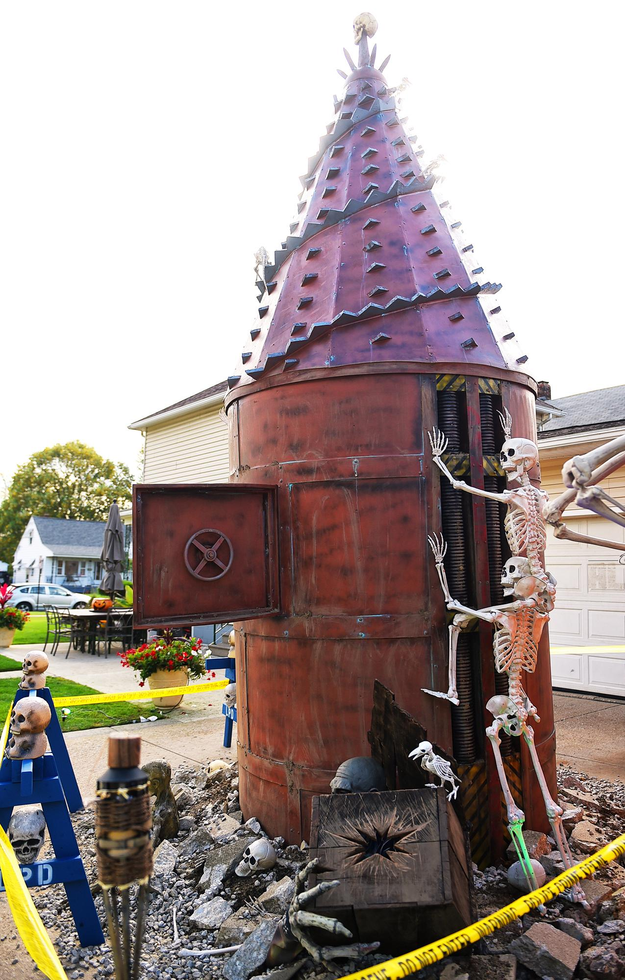 In an Oct. 12, 2017 photo, Ricky and Marlene Rodriguez's home at the corner of 30th St. and Tacoma Ave., in Lorain, Ohio, has morphed from a pirate ship, to a train and now into a digging machine poking through the home's driveway. The home is an annual attraction for neighbors and passersby within the city.  (Kristin Bauer/Chronicle-Telegram via AP)