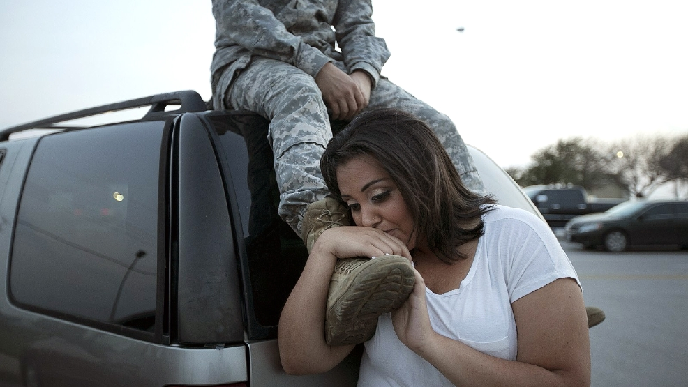 Lucy Hamlin leans on her husband's foot, Specialist Timothy Hamlin, as they wait to be allowed back onto Fort Hood, Texas, where they reside, Wednesday, April 2, 2014. (AP Photo/Austin American-Statesman, Deborah Cannon)