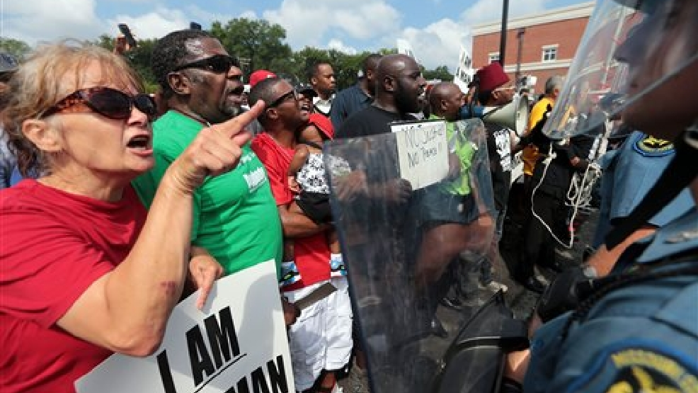 """This is an shooting of an 18-year boy who was supposed to start school today,"" said protestor Fiona Wilson of Ferguson , who shouts at the barricade of Missouri State Highway Patrol troopers in front of the Ferguson police station on Monday, Aug. 11, 2014. ""I don't want this to be appear as a racial thing. It's a police brutality issue. The officer used excessive force. It's not a black and white thing. That's why I am out here. I want more white people to come out,"" said Wilson. Marchers are entering a third day of protests against Saturday's police shooting of Michael Brown. (AP Photo/St. Louis Post-Dispatch, Laurie Skrivan)"
