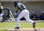 Milwaukee Brewers' Jean Segura runs with the bat as he steps over a fair ball he hits during the first inning of a spring training baseball game, Tuesday, March 18, 2014, in Phoenix.  Segura was thrown out at first base. (AP Photo/Ross D. Franklin)