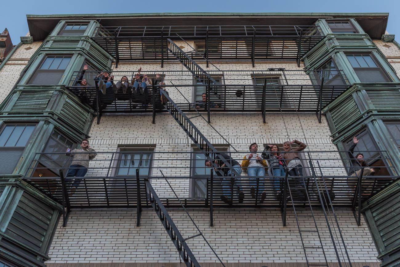 "Observers hang out on the fire escape of a Main Street building to watch the 26th annual Bockfest parade below. First published on March 3 in ""Photos: The 26th Annual Bockfest Parade"" / Image: Mike Menke"